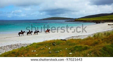 Four riders and horses on the Sellerna beach, Cleggan, in summertime, Ireland. - stock photo