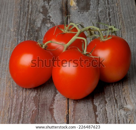 Four Ripe Raw Grape Tomatoes with Stems isolated on Rustic Wooden background - stock photo