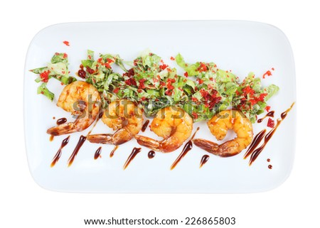 four roasted shrimps with green salad and tobiko on a white rectangular plate isolated on white background. Top view. - stock photo