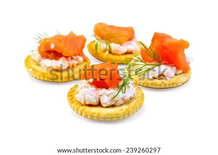 Four round crackers with cream, dill and salmon isolated on white background - stock photo