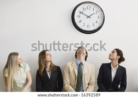 Four seated office workers looking at clock - stock photo