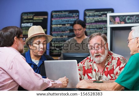 Four serious mature men in cafe with laptop - stock photo