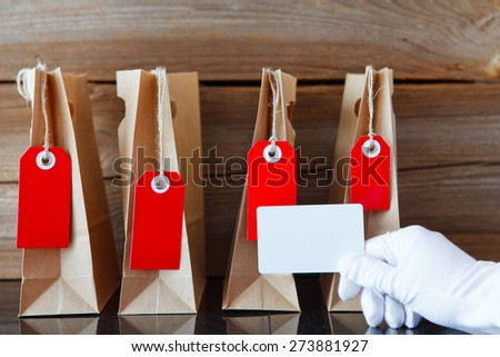 four shopping bags with a price tag and a hand showing a blank credit card in front - stock photo