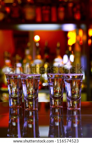 four shots of tequila with lime and salt on a wooden table bar on the background of bright lights of the bar - stock photo