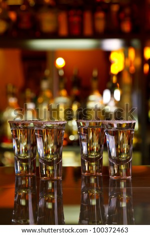 four shots of tequila with lime and salt on the table bar on the background of light bar - stock photo