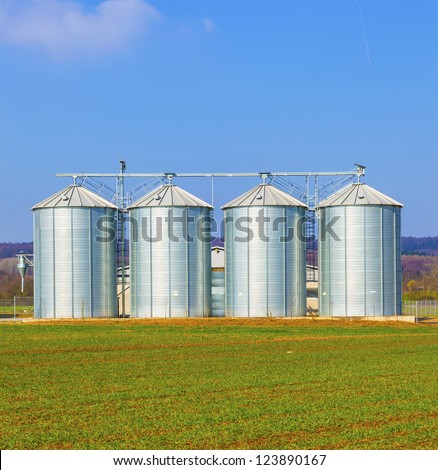 four silver silos in field under bright sky - stock photo