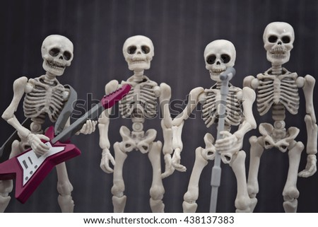 Four skeletons in rock band pose - stock photo