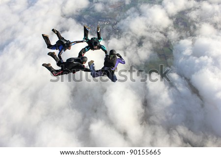 Four skydivers in freefall doing formations over a bank of clouds - stock photo
