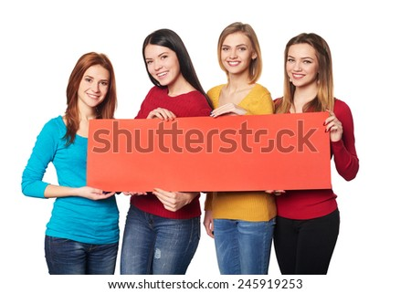 Four smiling girls friends showing red blank cardboard over white background - stock photo