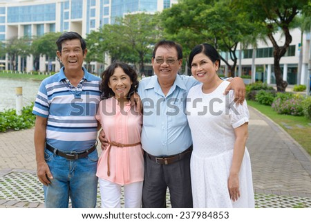 Four smiling senior people hugging and looking at the camera - stock photo