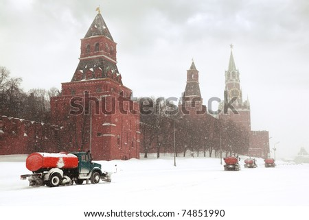 Four snow-remover trucks on the road near Kremlin chiming clock of the Spasskaya Tower in Moscow, Russia at wintertime during snowfall - stock photo