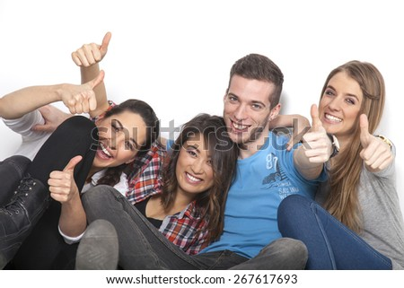 Four students hold up their hands with thumbs up - stock photo