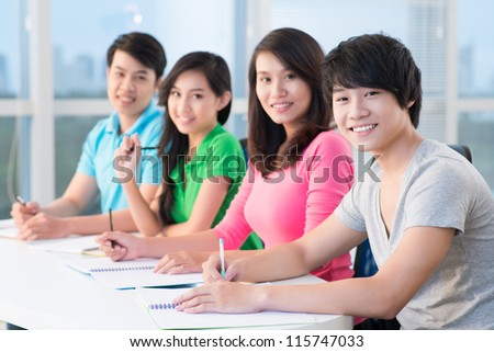 Four students sitting in classroom, the focus is on boy - stock photo
