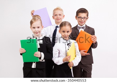 Four students smiling on a white background with books in their hands. - stock photo