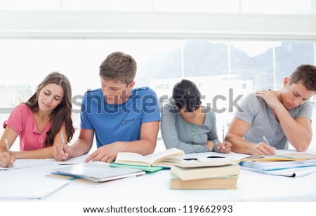 Four studying students sit beside each other and work hard - stock photo