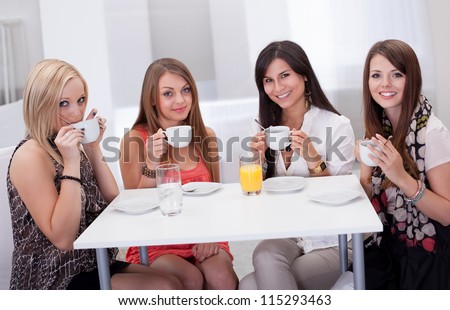 Four stylish young woman having coffee seated at a table with rows of colorful shopping bags on the floor beside them - stock photo