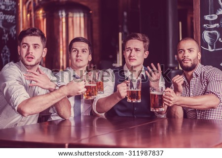 Four successful business people drinking beer and rejoice and shout together watching TV at the bar. Confident business people having fun with friends at the bar with a beer watching football on TV - stock photo