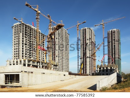 Four tall buildings under construction with cranes against a blue sky - stock photo