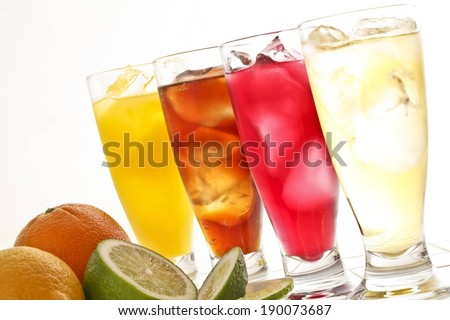 Four tall glasses of ice cold beverages beside sliced citrus fruit. - stock photo