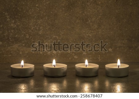 four tea candles on gray concrete background - stock photo