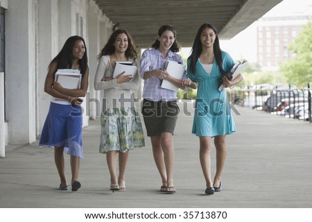 Four teenage girls holding books and hanging out in the school campus - stock photo