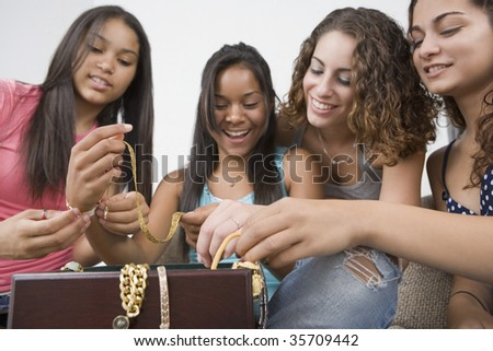 Four teenage girls holding jewelry and smiling - stock photo