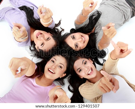four teenage girls lying on the floor pointing at camera - stock photo