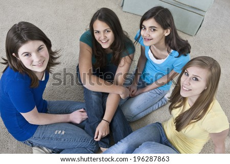 Four teenage girls relaxing in a group together on a living room carpeted floor - stock photo