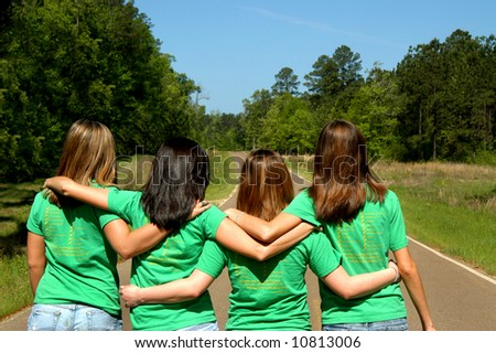 Four teens dressed in matching green tee shirts walk down a highway together arms locked. - stock photo