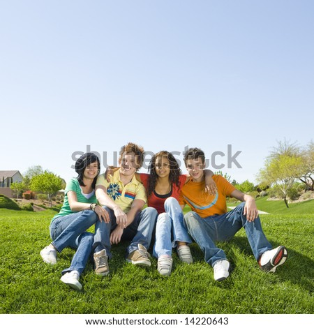 Four teens hang out in a park - stock photo