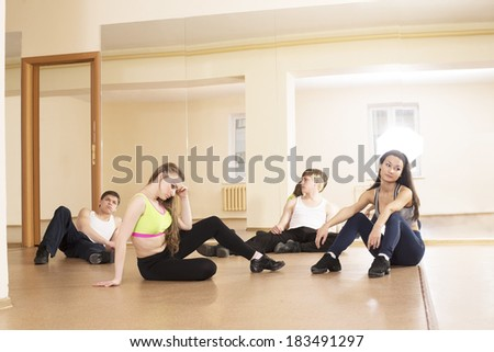 Four tired people sitting on Low section of two women and couple man relaxing in ballet rehearsal room on yellow wall with mirror reflection background - stock photo