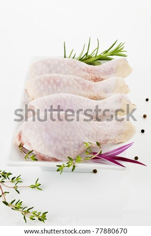 Four uncooked chicken legs on white plate decorated with rosemary and pepper corns. - stock photo