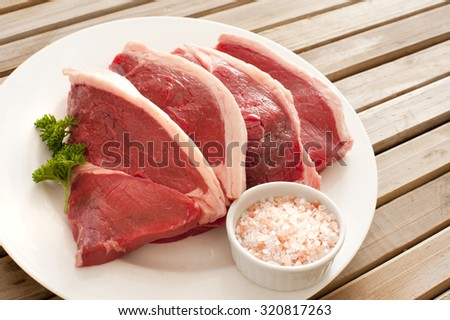 Four uncooked succulent beef steaks arranged ready for cooking on a plate with a bowl of rock salt and parsley garnish - stock photo