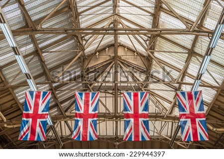 Four 'Union Jacks' hanging from the roof top in London's Victoria Station - stock photo