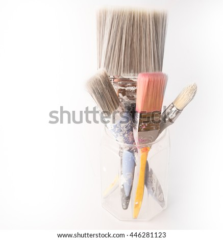 Four used decorating paintbrushes in a glass jar still splashed with paint - stock photo