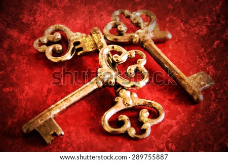 Four vintage keys. Retro aged toned photo with scratches. - stock photo