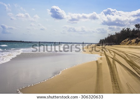 Four wheel drive tracks on sandy beach with boats and vehicle in distance. - stock photo
