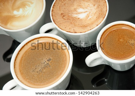 four white coffe cups on the black background - stock photo