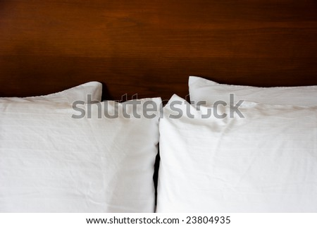 Four white fluffy pillows lay symmetrically against a solid wood stained headboard. - stock photo