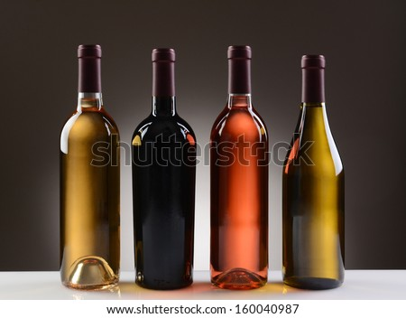 Four Wine Bottles with no labels on a light to dark gray background. Four different wines including: Cabernet Sauvignon, Chardonnay, Sauvignon Blanc, and White Zinfandel. - stock photo