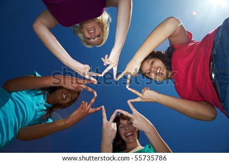 Four women forming a star shape with their fingers - stock photo