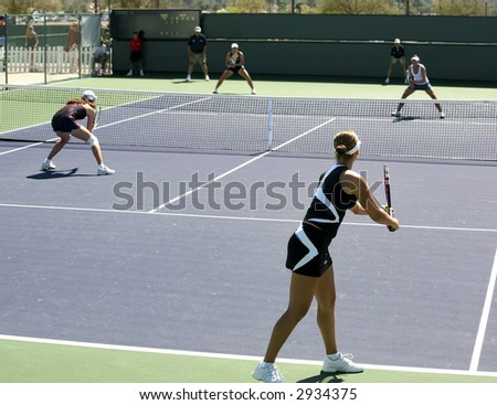 Four women playing doubles at the professional tournament - stock photo
