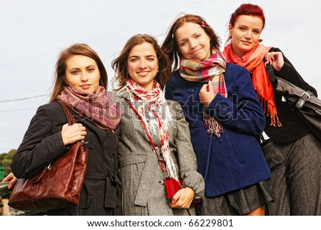 four women walking along the street together - stock photo