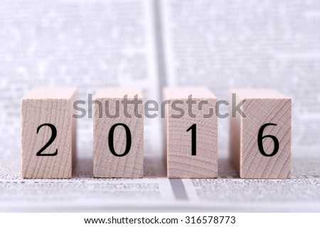 Four wooden blocks with 2016 numerals on newspaper background. - stock photo