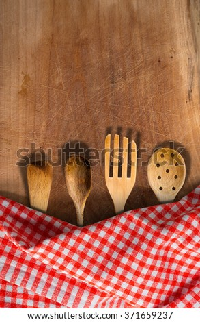 Four wooden kitchen utensils, fork, spoons and ladles on a wooden table with red and white checkered tablecloth - stock photo