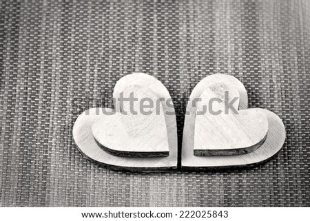 Four wooden white heart shapes on textile background. Monochrome Color. - stock photo