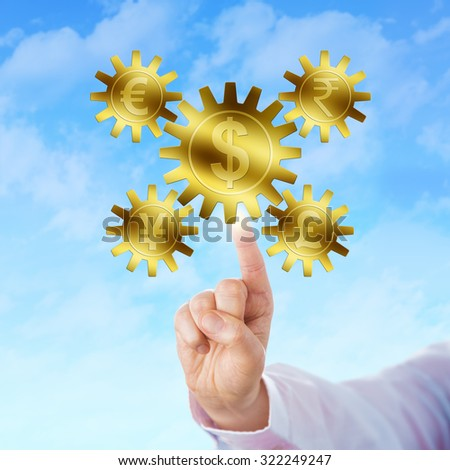 Four world currencies represented by golden cog wheels are interlocking with the Dollar symbolized by a large gearwheel. A raised index finger is touching the gig cog at the center of the gear train. - stock photo