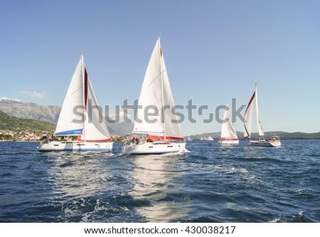 "Four yachts under sail. Tivat, Montenegro - 26 April, 2016. Regatta ""Russian stream"" in God-Katorskaya bay of the Adriatic Sea off the coast of Montenegro. - stock photo"