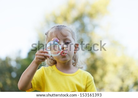 Four year old beauty blowing bubbles skyward - stock photo