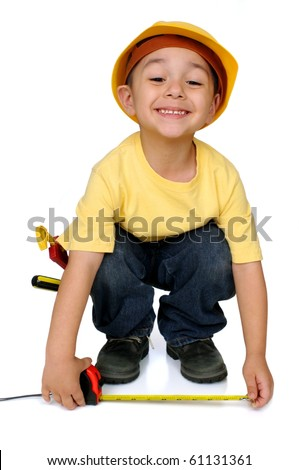 Four-year-old boy dressed as  construction worker uses his tape measure, isolated on white background - stock photo